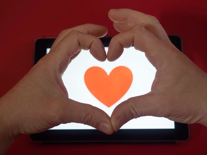 Cropped Hands Making Heart Shape Over Device Screen