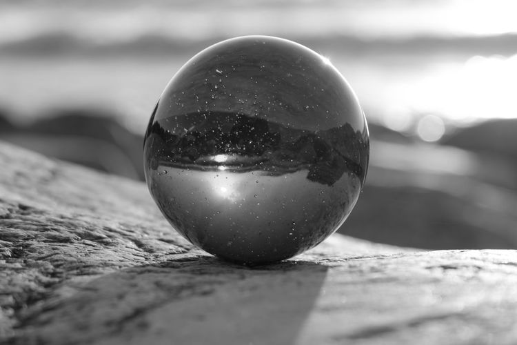 Close-up of crystal ball on rock outdoors