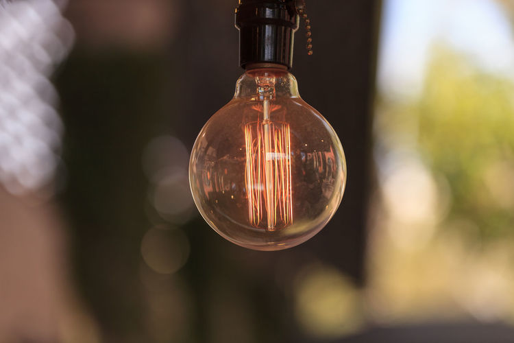 Ornamental light bulb lit up and hanging from the ceiling with a modern kitchen in the background, representing a rustic concept of success and inspiration. Backgrounds Bulb Electric Electricity  Glow Idea Illuminated Inspiration Kitchen Light Light Bulb Lights Ornamental Success