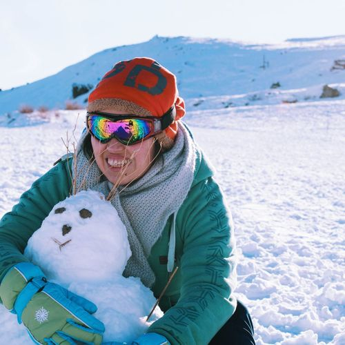 Smiling Woman Wearing Warm Clothing Embracing Snowman During Winter