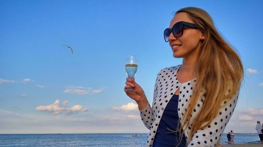 Young Woman Holding Wineglass At Sopot Beach Against Sky
