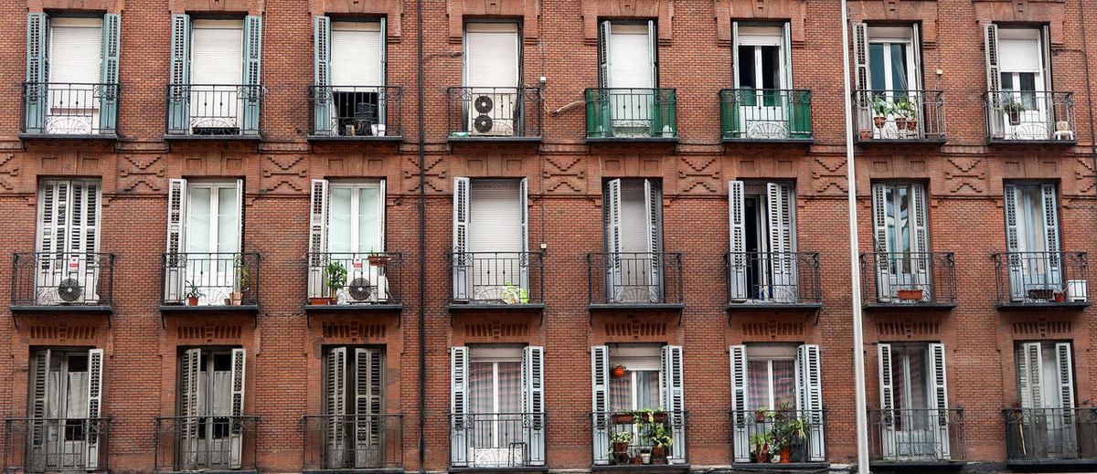 Red brick facade with wrought iron balconies in madrid, spain