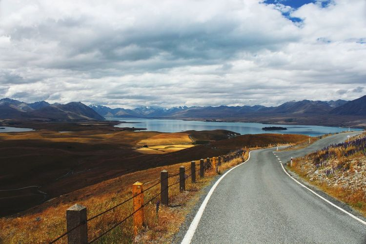 Empty road by lake against cloudy sky