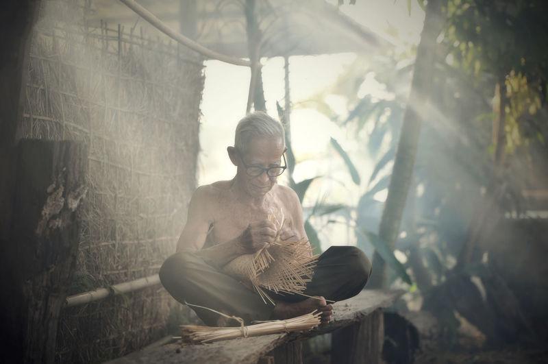 Senior man making wicker basket on sunny day