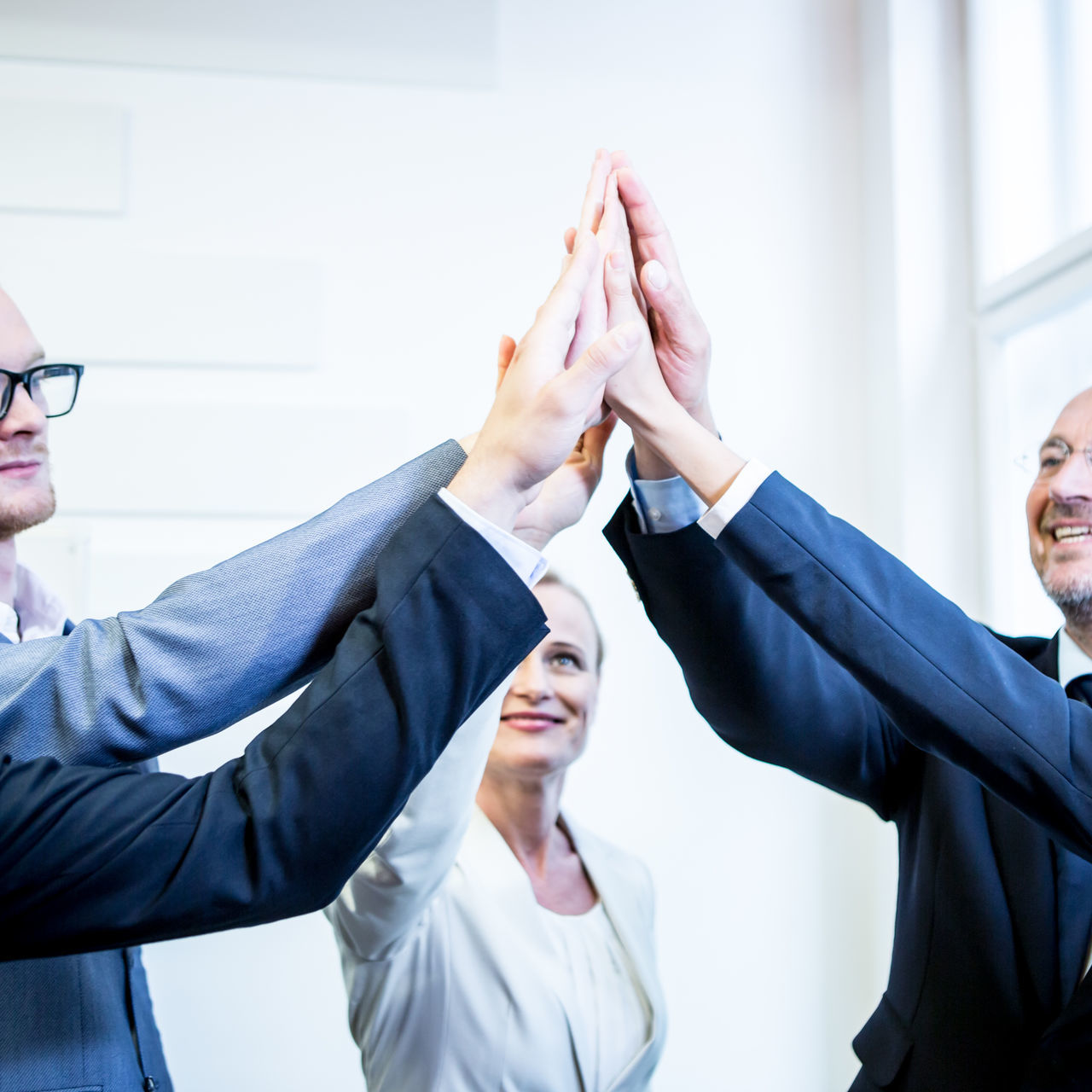 Business People Doing High-Five In Office