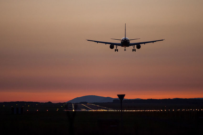 Airplane landing on sunset. Budapest, Hungary Air Air Vehicle Airplane Airport Airport Fence Airport Runway Commercial Airplane Fence Flying Helicopter Journey Mid-air Mode Of Transport Nature Night No People Orange Color Outdoors Public Transportation Runway Runway Lights Silhouette Sky Sunset Transportation