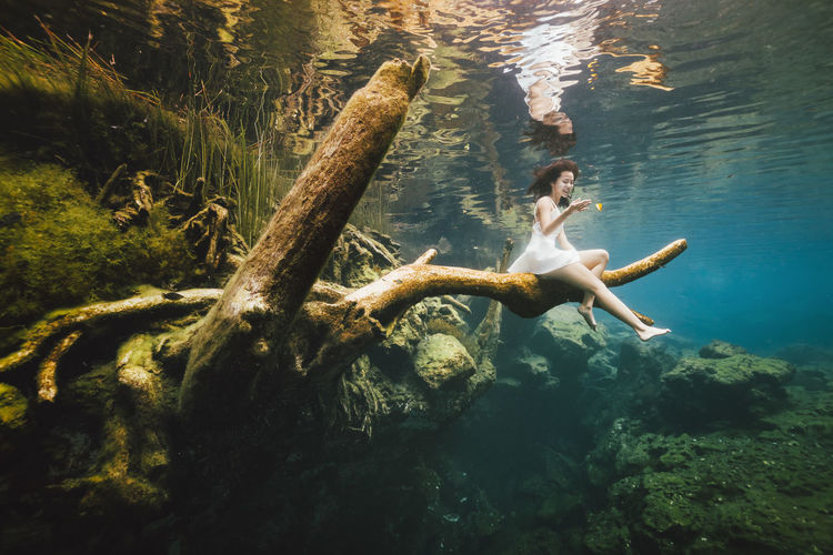 Low angle view of woman sitting on branch underwater