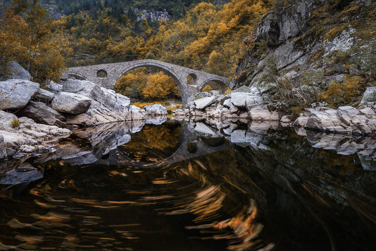 Devil's bridge, Bulgaria. Ancient stone bridge over Arda river, autumn time with leaves in water. Architecture Reflection River Motion Water Old Landscape Bridge Travel Autumn Stone Ancient Lake Devil Bulgaria Flowing No People Arch Bridge Rock Nature Solid Rock - Object Waterfront Day Tree Tranquility Outdoors Flowing Water Beauty In Nature Rock Formation Scenics - Nature Stream - Flowing Water Eroded Arda