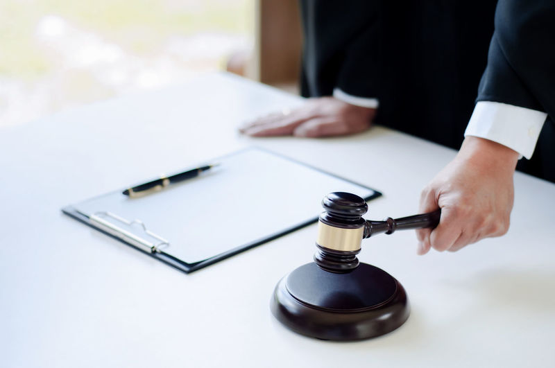 Midsection of lawyer holding gavel in courtroom