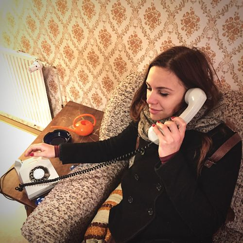 High angle view of woman talking on rotary phone at home