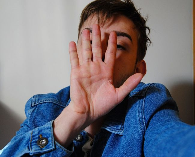 Portrait young man covering face with hand