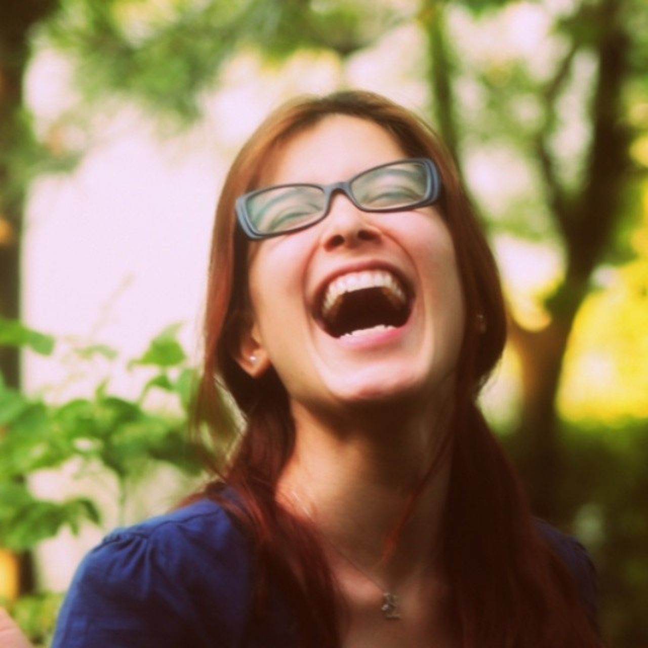 front view, focus on foreground, eyeglasses, one person, mouth open, real people, outdoors, tree, headshot, young adult, happiness, day, close-up, young women, smiling, one young woman only, nature, people, adult, adults only