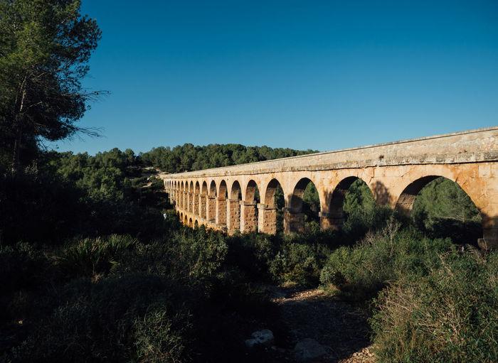 Arch bridge against clear blue sky
