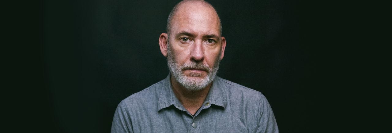 Portrait of mature man against black background