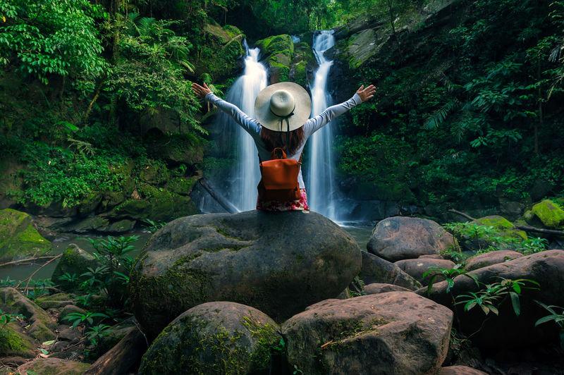 Full length of man standing on rocks in forest