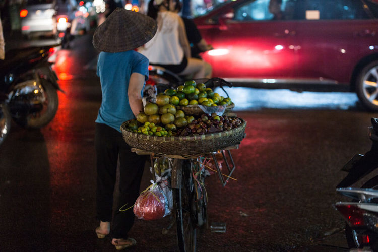 Rear View Of Woman Transporting Fruit On Bicycle