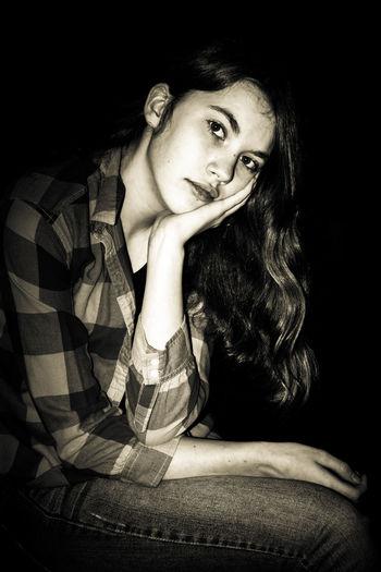Portrait of woman sitting against black background