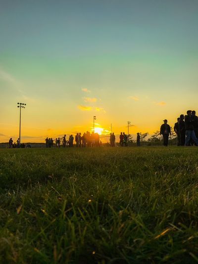 Sky Sunset Field Land Plant Grass Environment Nature Landscape Beauty In Nature Group Of People Orange Color Real People Scenics - Nature Growth Outdoors Tranquil Scene Rural Scene Tranquility Men