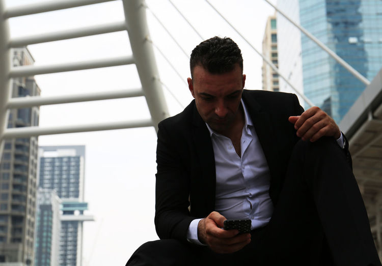 Tensed businessman using mobile phone in city