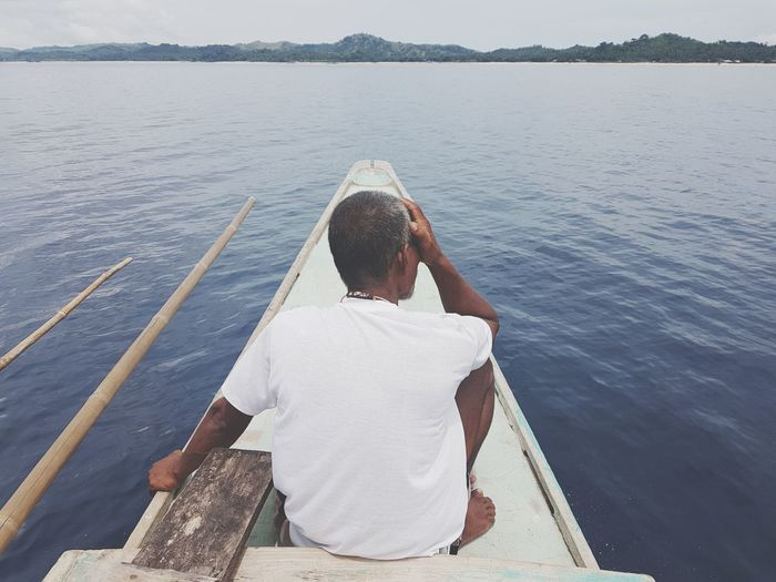 Rear View Of Man Sitting On Boat In Sea