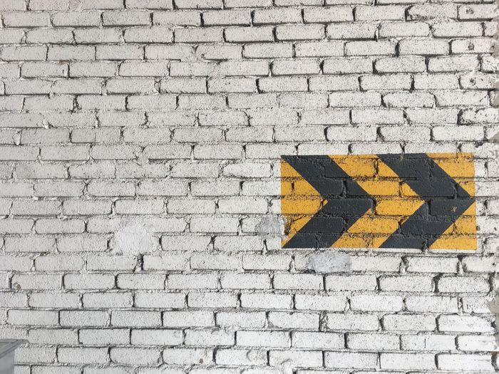 Arrow Symbols On Brick Wall