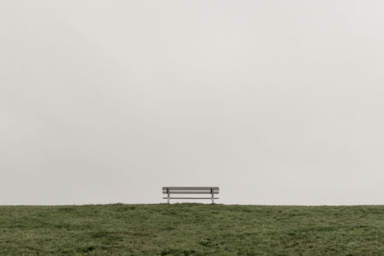 Empty bench on field against clear sky