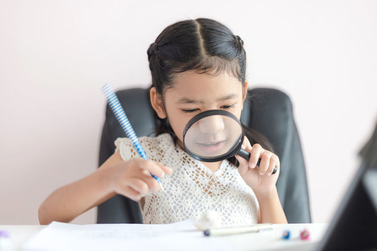 Cute girl looking through magnifying glass against white background