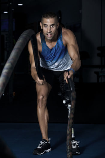Determined disabled man exercising with battle ropes at gym