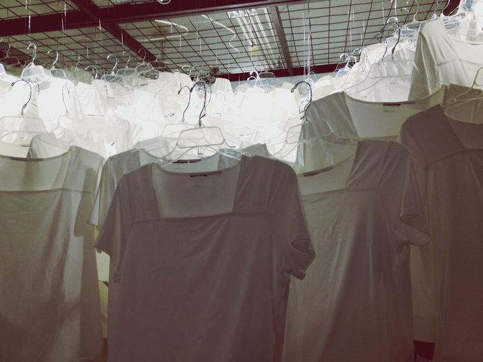 Close-up of white color dresses hanging in coat hangers