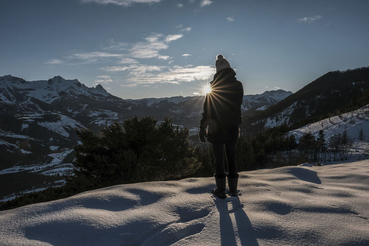 Person standing on snow covered mountain against sky