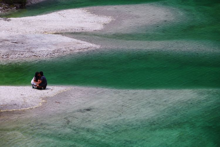 Couple sitting on shore at beach