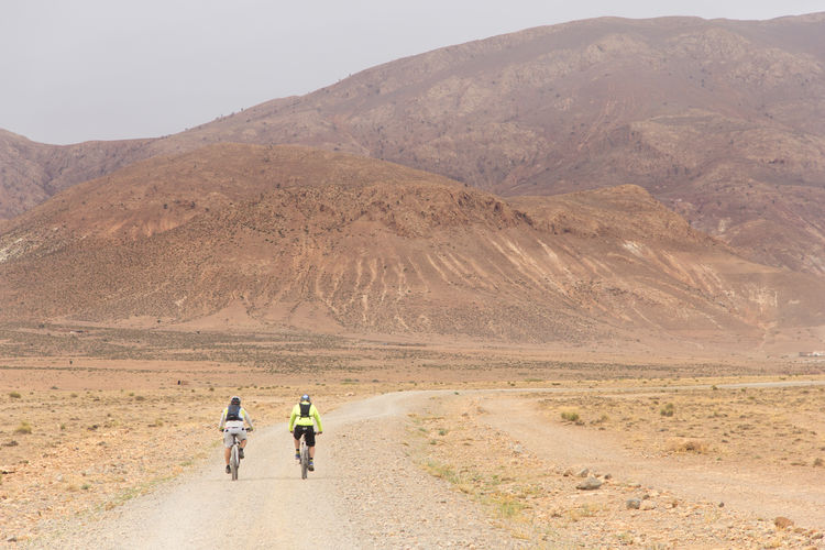 Rear view of people cycling on road against mountain