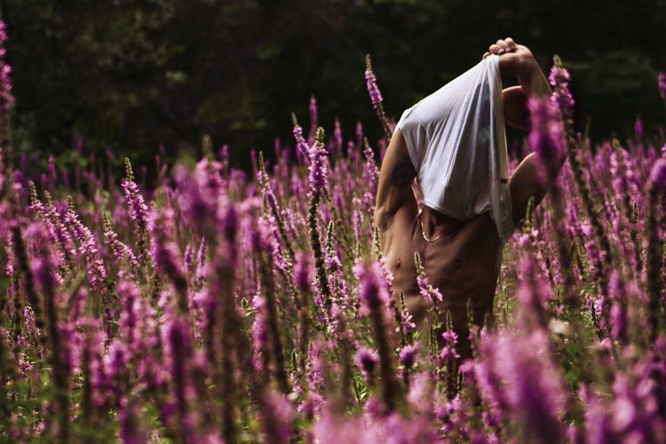 Man removing t-shirt while standing amidst plants