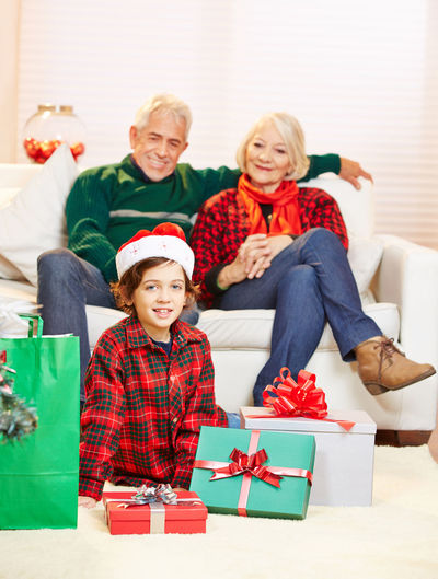 Portrait Of Smiling Boy With Grandparents While Sitting On Sofa During Christmas At Home