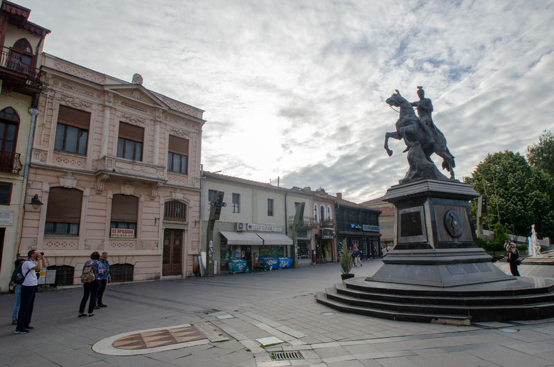 Statue against historic building in city against sky