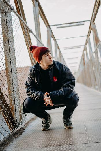 Full length of senior man sitting on fence