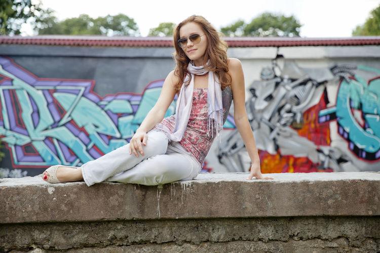 Full Length Of Woman Sitting Against Graffiti Wall