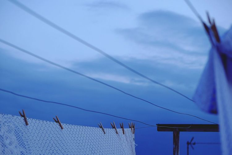 Close-up of clothes drying against the blue sky