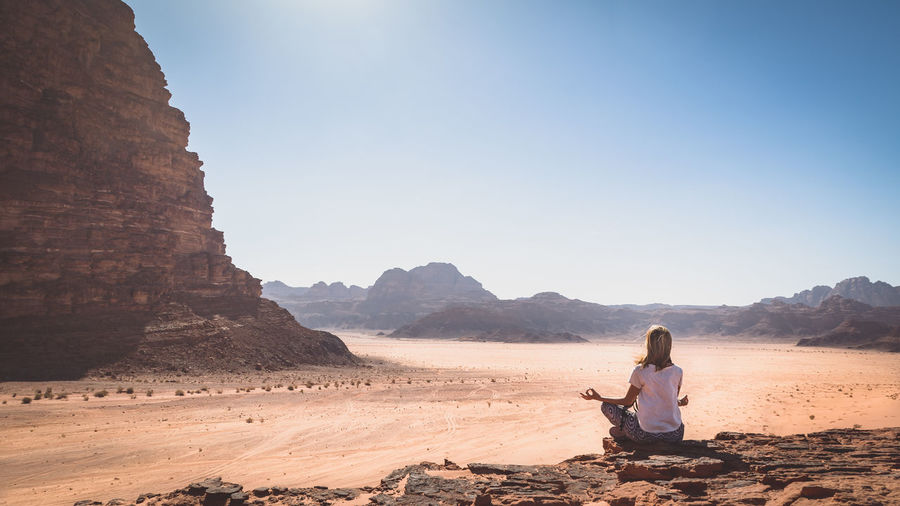 Woman meditating on landscape against clear sky