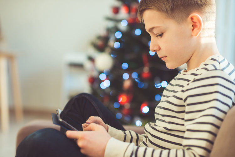 Boy using digital tablet at home during christmas