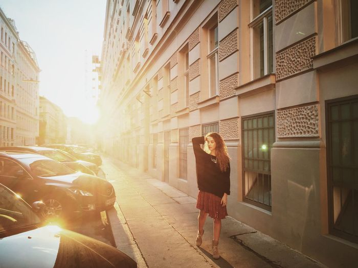 Young Woman Walking On Sidewalk By Building In City