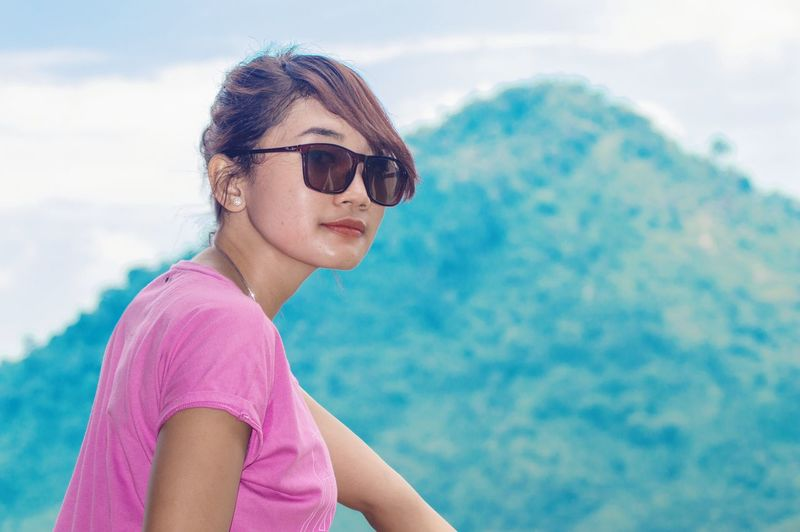 Portrait of woman wearing sunglasses against mountain