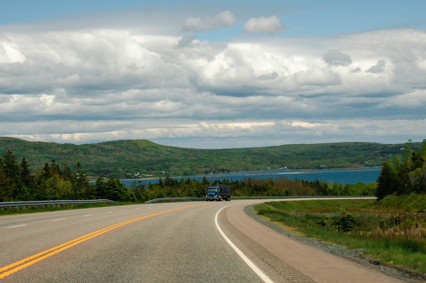 Driving the Cabot Trail on Cape Breton Island in Nova Scotia, Canada Cape Breton Highlands Nova Scotia, Canada Beauty In Nature Cape Breton Cloud - Sky Day Diminishing Perspective Direction Dividing Line Environment Landscape Nature No People Outdoors Plant Road Road Marking Scenics - Nature Sign Sky Symbol The Way Forward Tranquil Scene Transportation Tree