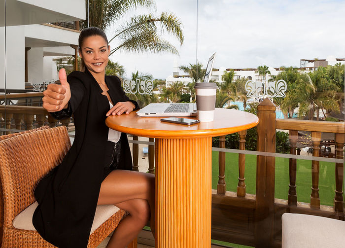 Young woman sitting on table at restaurant