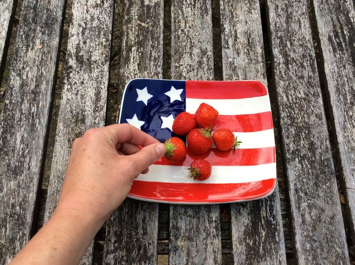 woman's hand grabbing strawberry from American flag themed plate 4th Of July Day Finger Food Food And Drink Freshness Hand Healthy Eating High Angle View Holding Human Body Part Human Hand Leisure Activity Lifestyles One Person Patriotism Personal Perspective Real People Red Unrecognizable Person Wood - Material