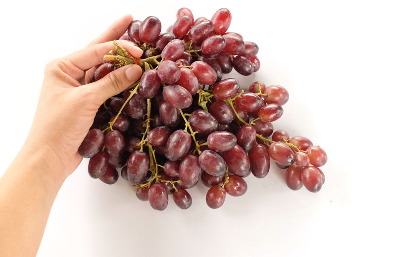 Close-up of hand holding grapes over white background