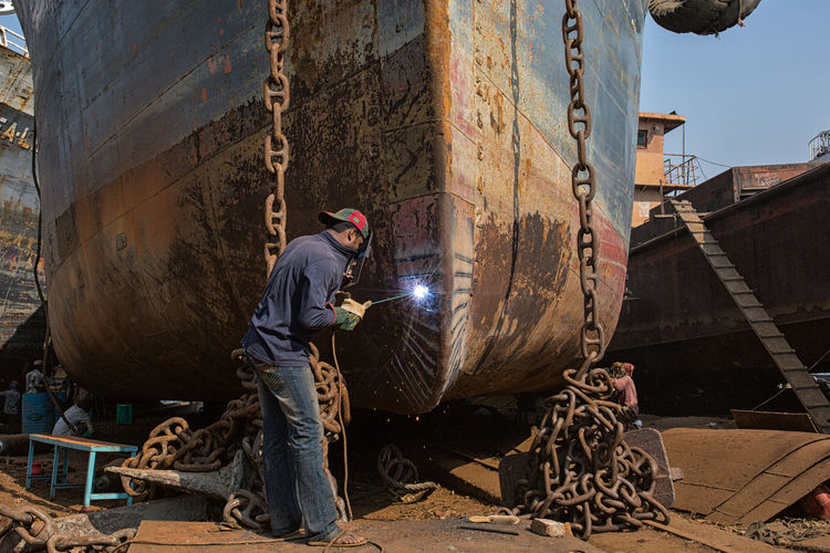 Side view of worker welding ship part at dry dock
