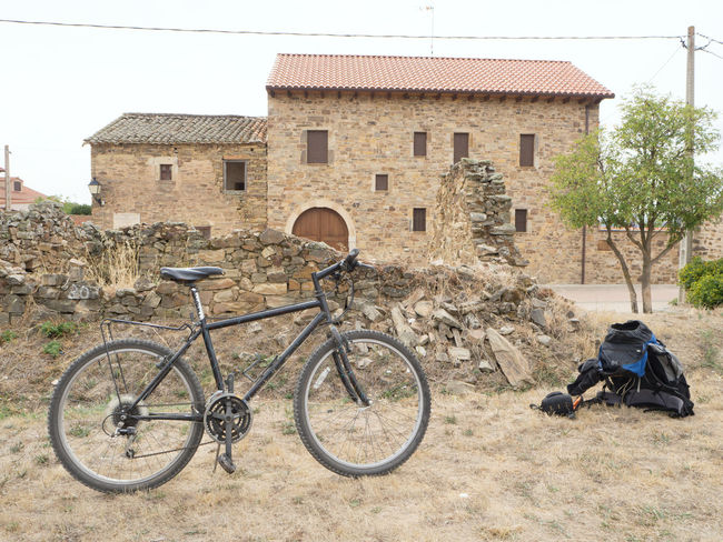 cycle and a backpack in a village on the Way Of Saint James / Camino De Santiago Arid Climate Bike Bycicle Camino De Santiago Cycle Outdoors Parked Rest SPAIN Tour Trekking Village Way Of Saint James