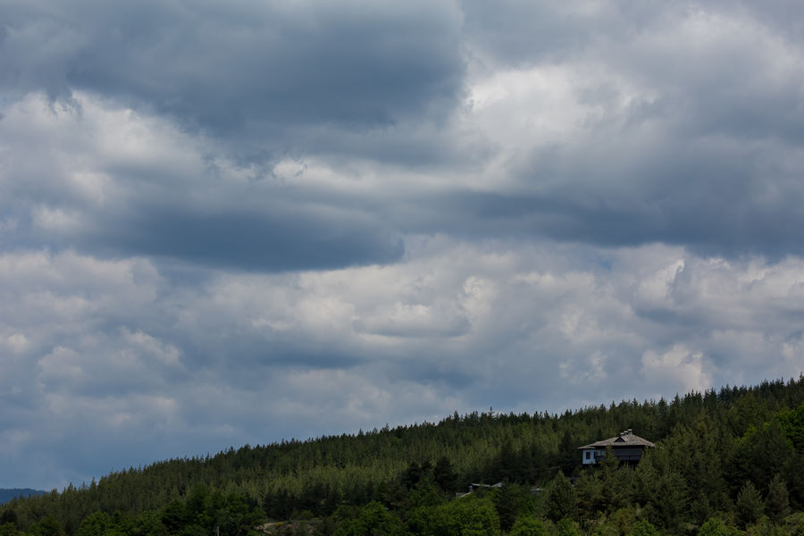Lonely traditional Bulgarian white Rhodope house with tiled roof under heavy clouds in green pine tree forest Kovachevitsa Kovachevitza LeshtenBulgaria Rhodopes Beauty In Nature Bulgaria Cloud - Sky Day Growth Landscape Leshten Nature No People Outdoors Pirin Rhodopemountains Scenics Sky Storm Cloud Tranquil Scene Tranquility Tree