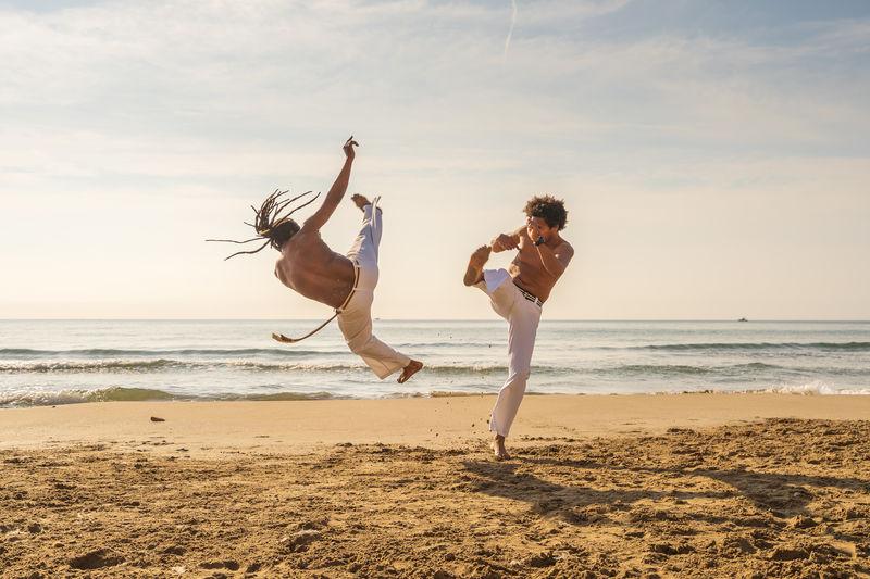 Men practicing capoeira at beach